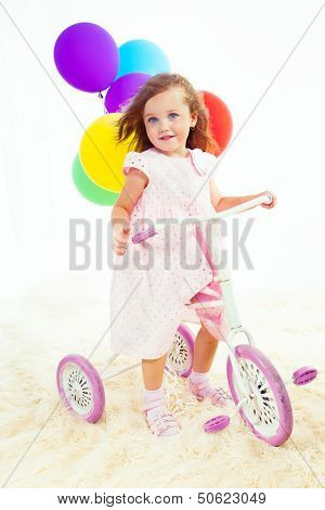 Sweet preschool girl on a white and pink vintage kids three wheeler