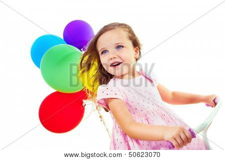 Portrait of a cheerful little girl on a bike, with colorful balloons behind