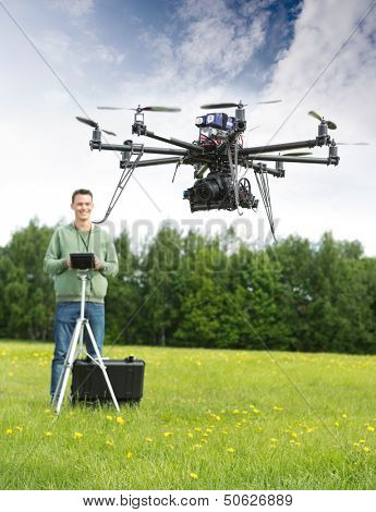 Young man with remote control flying UAV helicopter in park