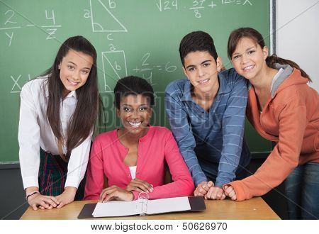 Portrait of young teacher with high school students at desk in classroom