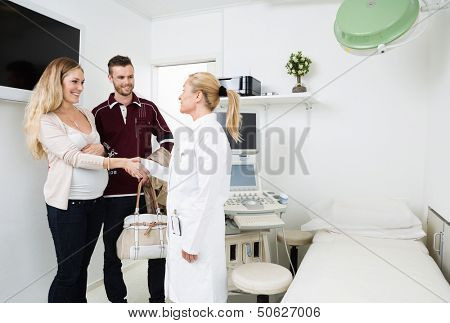 Mid adult female gynecologist greeting happy young expectant couple in clinic