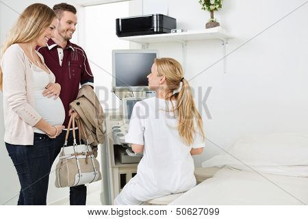 Young female doctor looking at expectant couple while using ultrasound machine in clinic