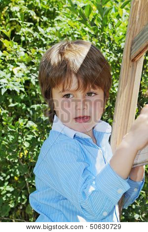 The spoiled beautiful green-eyed boy climbed up a wooden sliding ladder and doesn't want to go down