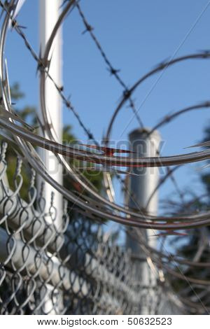 Large metal fence with barbwire and razor wire