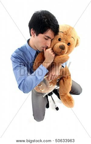 Businessman hugging teddy bear