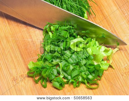 Sliced Greens With Knife On Wooden Cutting Board