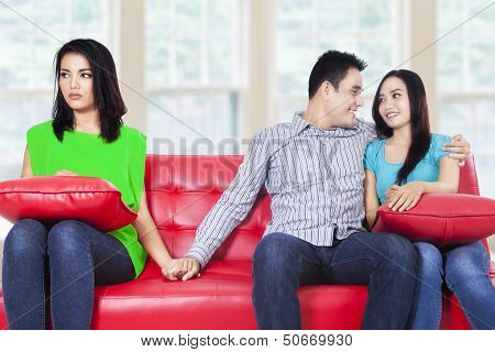 A Woman Holding Hands With Man Sitting Near His Girlfriend