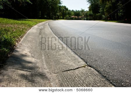 Low Angle View Of Road Surrounded By Trees With Water Run Off Groove