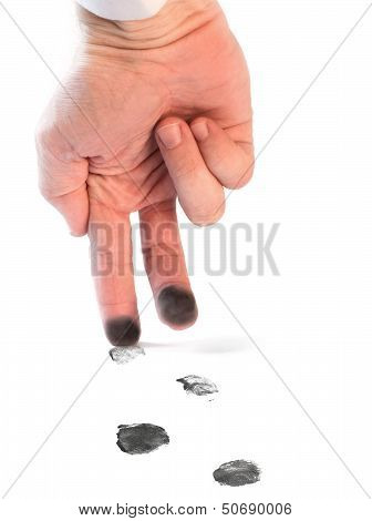Man's Hand With Stained Fingers Walking On The White Sheet With Black Footprints. Fingerprints As A
