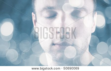 Sleeping Young Caucasian Man With Closed Eyes And Blurred Lights On Blue Background