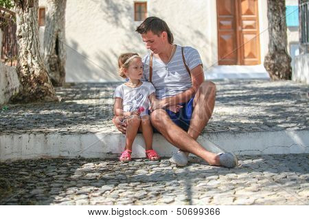 Young Father With Little Daughters Have A Rest On Street In Old Greek Town