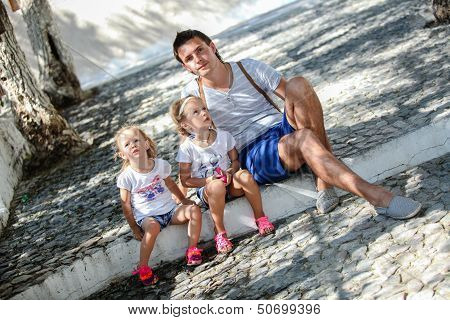 Young Father And Cute Daughters Sitting On Street In Old Greek Town