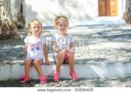Young Charming Girls Sitting At Street In Old Greek Village Of Emporio, Santorini