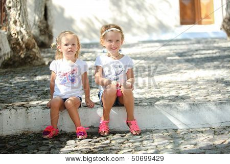 Little Cute Sisters Sitting At Street In Old Greek Village Of Emporio, Santorini