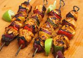 Chicken tikka kebabs with red onion and peppers.