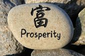 stock photo of prosperity  - Positive reinforcement word Prosperity engrained in a rock - JPG
