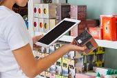 stock photo of supermarket  - Midsection of young woman scanning barcode through digital tablet at supermarket - JPG