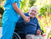 stock photo of amputation  - Old patient sitting in wheelchair holding the doctor - JPG