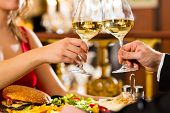 stock photo of restaurant  - happy couple have a romantic date in a fine dining restaurant they drink wine and clinking glasses - JPG