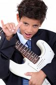 A little boy playing guitar