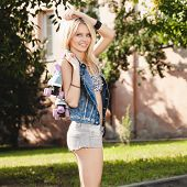 image of roller-derby  - Young woman standing with roller skates - JPG