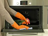 stock photo of oven  - Cleaning the oven with detergent and rag - JPG
