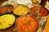 stock photo of curry chicken  - Selection of indian food with pilau rice naan bread poppadoms and samosas a popular choice for eating out in european countries - JPG