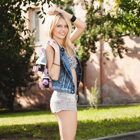 pic of roller-derby  - Young woman standing with roller skates - JPG