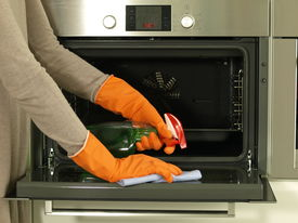 stock photo of detergent  - Cleaning the oven with detergent and rag - JPG