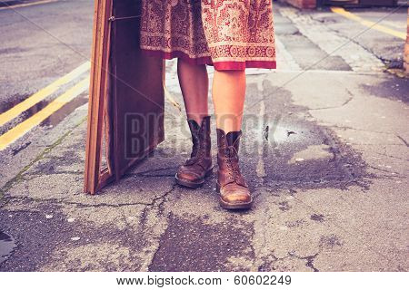 The Legs Of A Young Woman Standing In The Street With Picture Frame