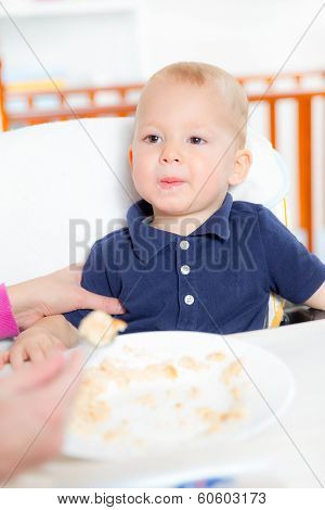 Mother feeding hungry baby in the highchair indoors