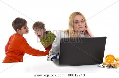 busy, working mother with computer while her kids fighting at background