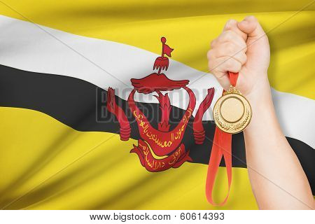 Medal In Hand With Flag On Background - Nation Of Brunei, Abode Of Peace