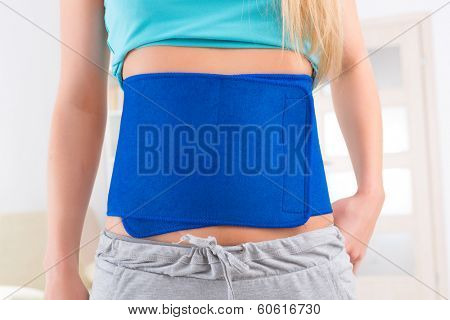 Woman wearing neoprene slimming belt at home