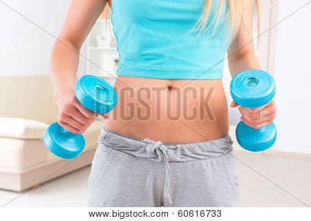 Woman with dumb bells standing at her home.