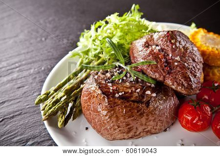 Piece of red meat steak with rosemary served on black stone surface.