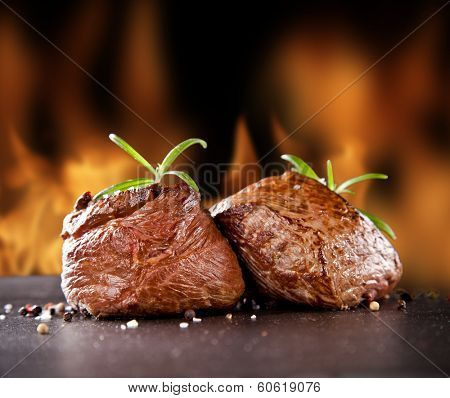 Pieces of red meat steaks with rosemary served on black stone surface. Blur fire flames on background