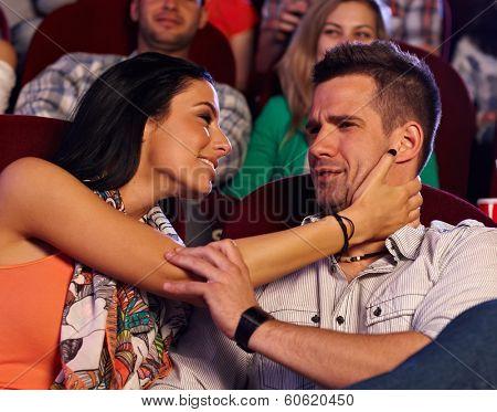 Young woman molesting man sitting next at cinema.