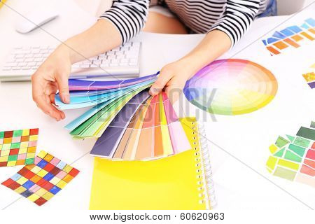 Woman designer selects color in workplace
