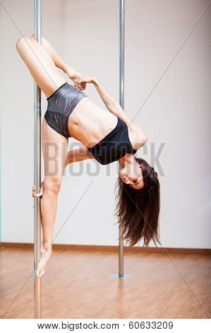 Athletic woman doing pole fitness