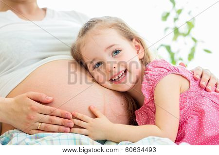 Happy Kid Girl Hugging Pregnant Mother's Belly