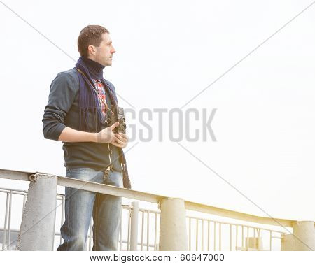 Young Man With Vintage Camera On A Jetty