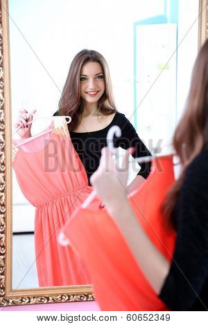 Young beautiful woman trying dress front of mirror in room