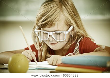 Cheerful hipster vintage little girl at school room having education activity