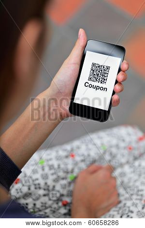 Woman hand holding mobile phone with QR code coupon