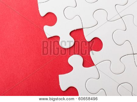Incompleted white puzzle with red background