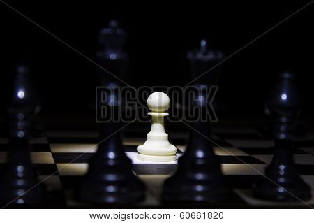White Pawn Standing Alone In Spotlight On Chess Board With Black Pieces