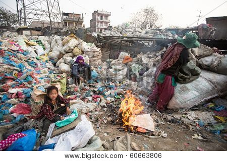 KATHMANDU, NEPAL - DEC 19, 2013: Unidentified child is sitting while her parents are working on dump. In Nepal annually die 50,000 children, in 60% of cases - malnutrition.