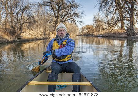 senior canoe paddler in a  canoe on the Cache la Poudre River, Fort Collins, Colorado, winter or early spring, view from the bow