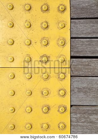 Yellow tactile strip for cane or foot of blind person